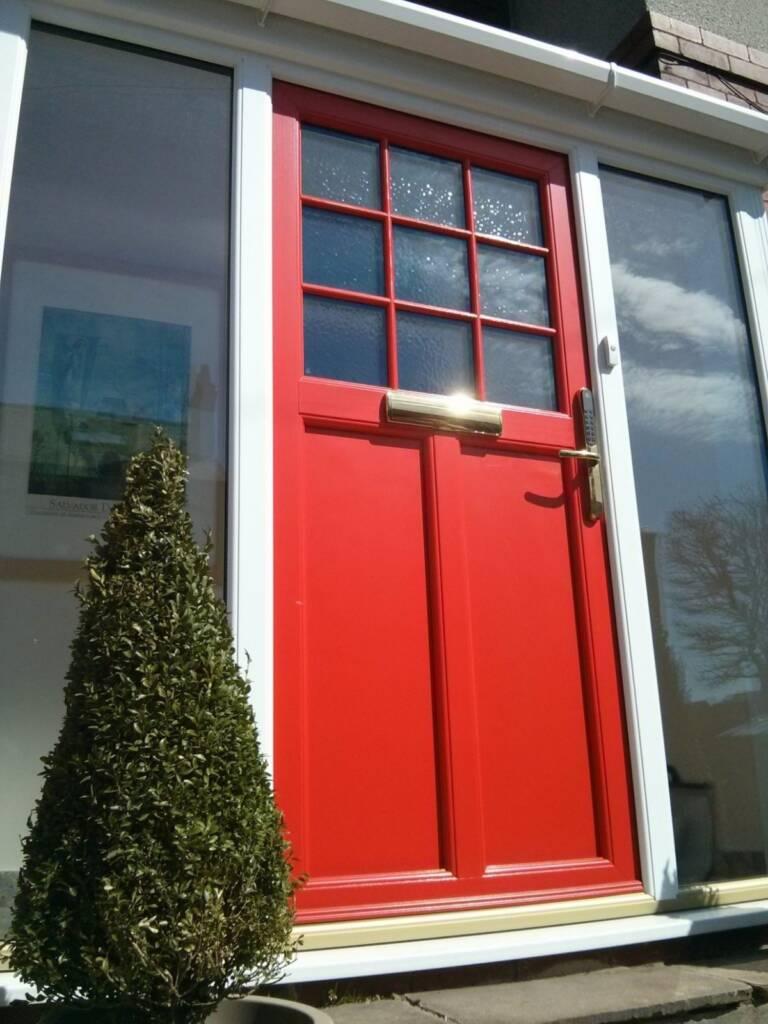 Sprayed burnt orange door in traditional door style. Part of a brand new front porch.